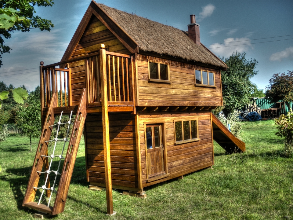 Front-left view (Elm House children's wooden play house : playhouse two storey custom built UK with slide and climbing net)