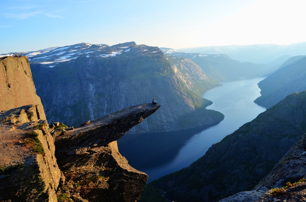 Holding The Boy Who Was Afraid of the World paperback while dangling feet over the edge of Trolltunga, Norway